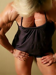 Mature female bodybuilder Clarkflex showing off the muscles in her pecs, big biceps, tight abs, musc...